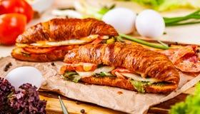 Croissants met bacon, kaas en groenten op houten raad stock afbeelding