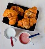 Croissants met boter en graangewassen met een kop van melk en strawb Stock Afbeeldingen