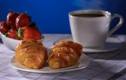 Croissants met koffie en aardbei op een blauwe achtergrond stock fotografie