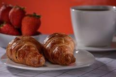 Croissants met koffie en aardbei op een rode achtergrond royalty-vrije stock foto