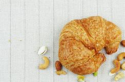 Croissants on tablecloth. Croissants and nuts on a tablecloth Stock Photos