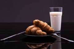 Croissants op een plaat met een glas melk Stock Afbeeldingen
