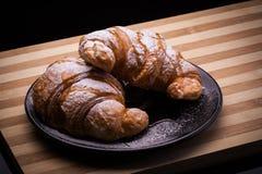 Croissants op een plaat met gepoederde suiker Stock Afbeeldingen