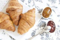 Croissants op lijst met jam, jus d'orange en koffie stock afbeelding