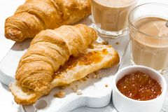 Croissants with orange jam and coffee with milk for breakfast. Closeup top view Royalty Free Stock Image