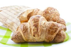 Croissants in paper pack on plate isolated Royalty Free Stock Image