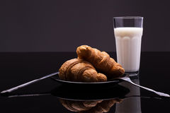 Croissants on a plate with a glass of milk. French breakfast; two croissants on a plate with a glass of milk stock images