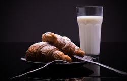 Croissants on a plate with powdered sugar and glass of milk. French breakfast; two croissants on a plate with powdered sugar and glass of milk royalty free stock image