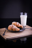 Croissants on a plate with powdered sugar and glass of milk. French breakfast; two croissants on a plate with powdered sugar and glass of milk Stock Photo