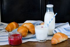 Croissants on a plate, raspberry jam, milk in a bottle and in a glass with a straw on a linen towel on a wooden table. The concept stock image
