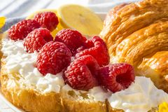 Croissants with raspberries and whipped cream for breakfast. Croissants with raspberries and whipped cream for sunny spring breakfast with coffee and lemon Stock Photos