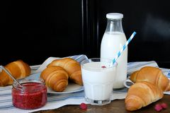 Croissants, raspberry jam, milk in a bottle and in a glass with a straw on a linen towel on a wooden table. The concept of healthy stock photos