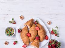 Croissants and ripe stawberries stock image