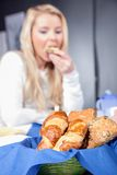 Croissants and rolls. Fresh baked croissants and rolls served in a breadbasket at breakfast with shallow dof and a blurred woman enjoying her meal in the Royalty Free Stock Images