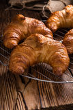 Croissants. Some fresh baked Croissants on vintage wooden background Royalty Free Stock Photography
