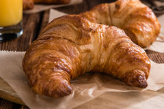 Croissants. Some fresh baked Croissants on vintage wooden background stock photos