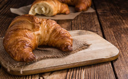 Croissants. Some fresh baked Croissants on vintage wooden background Stock Image