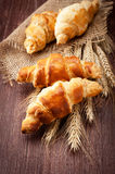 Croissants with spikelets of wheat on the wooden background Royalty Free Stock Photos