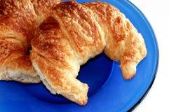 Croissants sulla lastra di vetro blu. fotografia stock libera da diritti