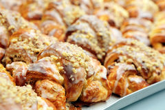 Croissants with sweet icing and walnuts in a bakery Stock Photos