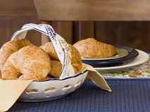 Croissants table setting. Fresh baked croissants in deruta ceramic basket with place setting in background royalty free stock photography