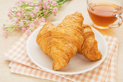 Croissants and tea cup on table, filtered image Royalty Free Stock Photo