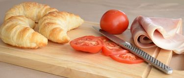 Croissants, Tomatoes and Ham on Wooden Board. Stock Images