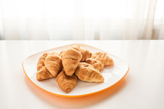 Croissants in a white plate. Mini croissants in a plate on a table with natural light Royalty Free Stock Images