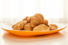 Croissants in a white plate. Mini croissants in a plate on a table with natural light Stock Photos
