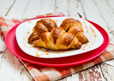 Croissants on the white plate. Croissants on the white and pink plate to pour caramel souce Royalty Free Stock Photo