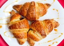 Croissants on the white plate. Croissants on the white and pink plate to pour caramel souce Stock Images