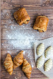 Croissants on a wooden table. Fresh and raw croissants on a wooden kitchen table stock photography