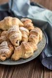Croissants z czekoladowym plombowaniem na drewnianym tle Zdjęcia Stock