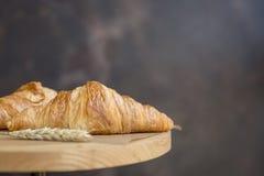 Croissants z pszenicznymi ucho przy ciemnym backgorund obraz stock