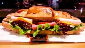 Croissantsandwich met ham, cheddarkaas, kersentomaat en greens stock afbeeldingen