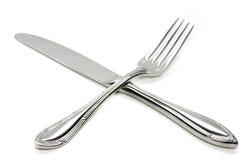 Croix argentée de fourchette et de couteau Photographie stock libre de droits