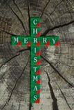 Croix avec l'inscription de Joyeux Noël composée des cubes avec des lettres sur le fond en bois photos libres de droits