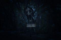 Croix avec le cri perçant de fantôme au-dessus de la forêt fantasmagorique à la nuit Image stock