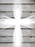 Croix blanche avec les rayons légers et le symbole chrétien de vieux fond gris en bois de la résurrection Image libre de droits