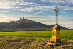 Croix catholique devant le château trosky au coucher du soleil, paradis de Bohème photographie stock