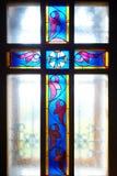 Croix catholique sur l'hublot (glace souillée) Photo stock