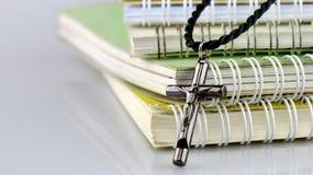Croix chrétienne argentée sur des livres Photo stock