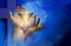 Croix chrétienne avec des mains libérant le papillon sensible  image stock