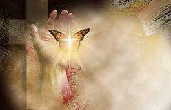 Croix chrétienne avec la main libérant le papillon rené sensible  photo stock