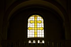 Croix chrétienne jaune faite de verre dans la fenêtre Symboles de la foi Crucifixion de Jésus image libre de droits