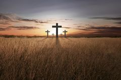Croix chrétienne lumineuse au coucher du soleil Photographie stock
