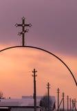 Croix chrétienne métallique et une rangée des poteaux électriques Photos stock