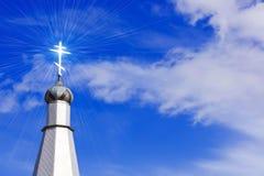 Croix chrétienne dans une flamme de lumière du soleil Images stock