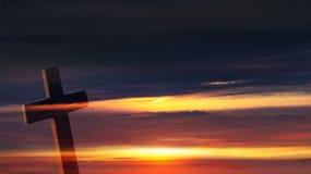 Croix chrétienne sur le fond de coucher du soleil photographie stock