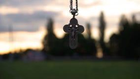 Croix chrétienne sur une chaîne sur le fond du lever de soleil banque de vidéos